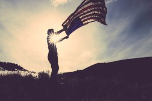 man holding american flag in the sunshine